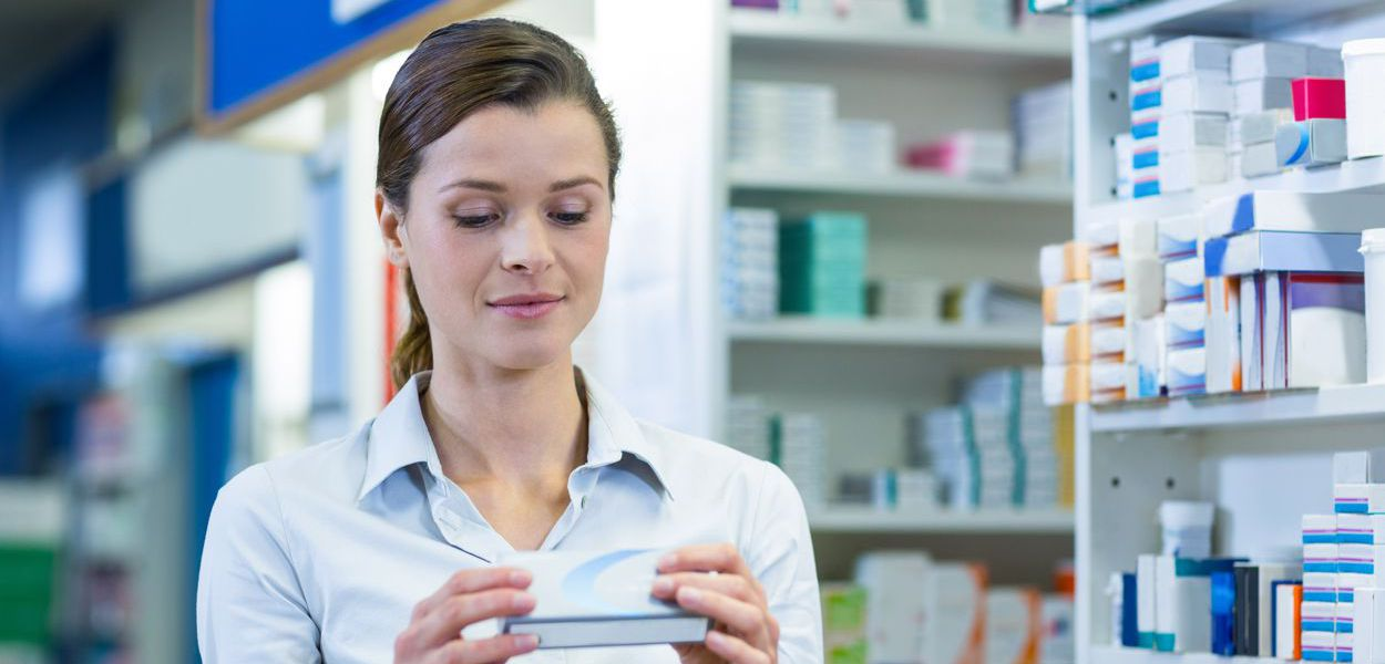 Woman reading pack of tablets in pharmacy